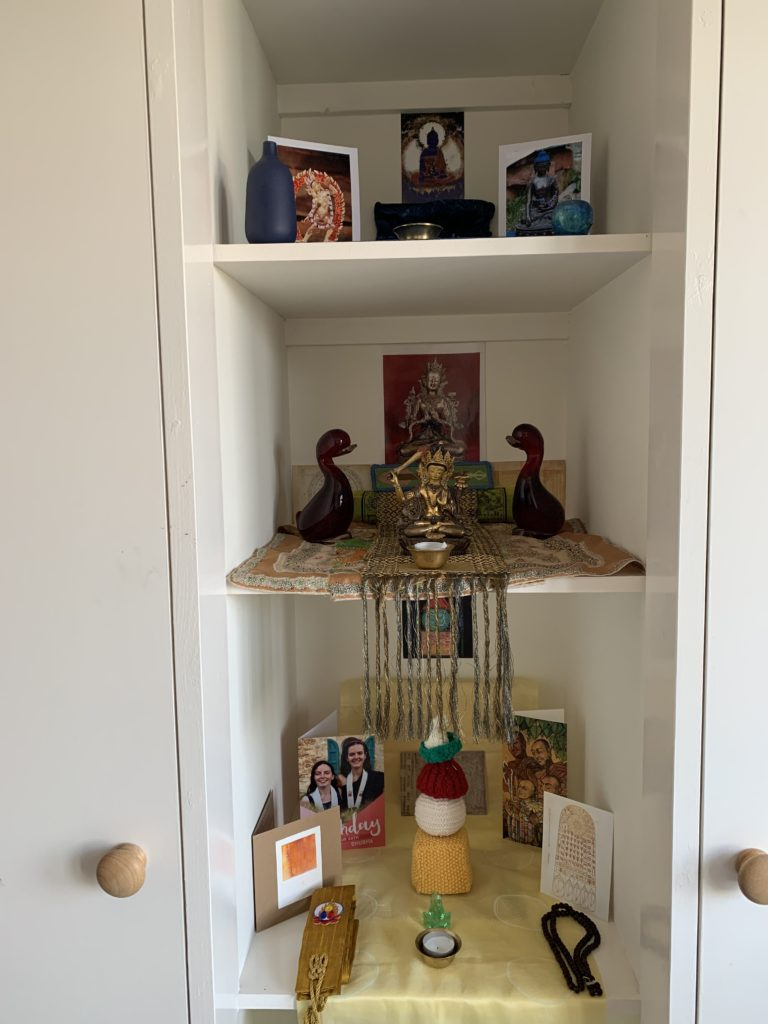 'This is a Trikaya, 3 Bodies of the Buddha shrine that is supporting me as I have relocated to my Mother's house. I am so glad I took a few shrine things with me and I had a number of Birthday cards. The Akshobhya, the blue wisdom Buddha, at the top represents the Dharmakaya. Then we have the Bodhisattva Manjusri, the Samboghakaya. The Nirmanakaya is the earthly Buddha so we have the knitted Stupa' Shubha
